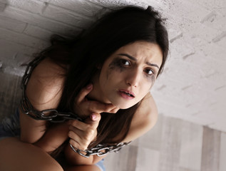 Woman with chained body sitting on floor