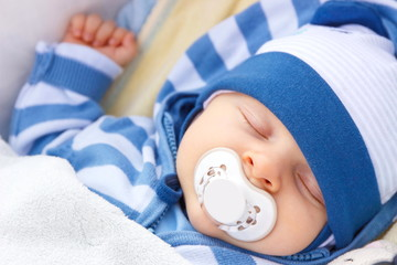 Newborn baby with pacifier sleeping in baby pram