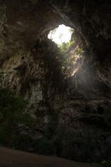 Sunlight shines through the  Than Lot Yai Cave ( Chaloem Rattanakosin National Park ) , Kanchanaburi, Thailand