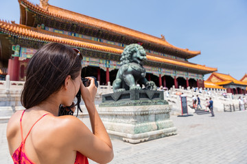 Tourist photographer taking pictures with camera of sculpture in front of ancient chinese temple, china. Asia summer travel, tourism destination popular attraction