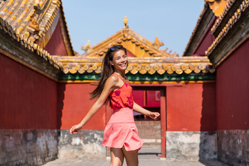 Wall Mural - Happy Asian caucasian mixed race woman tourist having fun running and dancing in traditional imperial chinese temple background. Girl enjoying china travel destination. Multiracial girl.