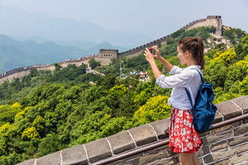 Wall Mural - Great Wall of china. Tourist taking photo at famous Badaling during travel vacation holidays at Chinese tourist destination. Woman tourist taking picture using smart phone in Asia.