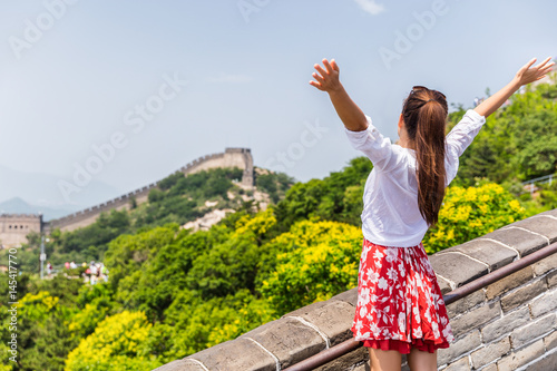 Wall mural Carefree woman tourist with arms up on Great Wall of china having fun at famous Badaling attraction during travel vacation in Beijing. Winning, success, freedom trousim concept.