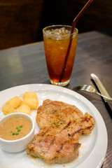 Pork steak with pepper sauce served with hash brown potato on white plate