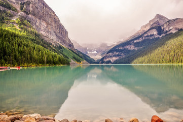 Rain starts at Lake Louise, one of the most beautiful alpine lakes in the Canadian Rockies, famous for the green-blue color of the water.