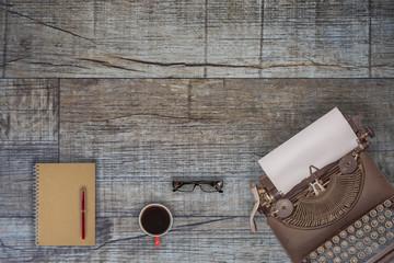 Vintage typewriter and coffee on wood background