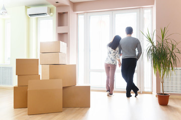 Happy young married couple with Unpackaged boxes holding new flat keys