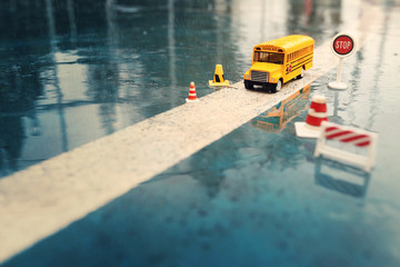 Yellow school bus toy model on the road with traffic signs,the rainy day.Travel / Education / Transportation concept background.
