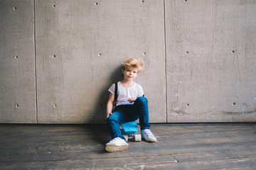 Little boy sitting on a skateboard at a wall