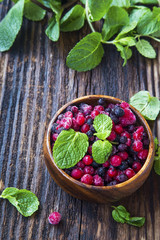 Fresh frozen fruits with mint leaves in wooden bowl