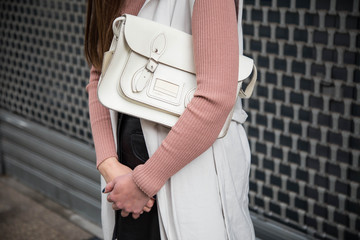Wall Mural - spring fashion outfit. european fashion blogger wearing a trendy white sleeveless overcoat, pink sweater, black leather skirt, ankle boots and a stylish white handbag. streetstyle detail