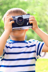 Happy cheerful boy with a camera, the baby photographed outdoors, soft focus