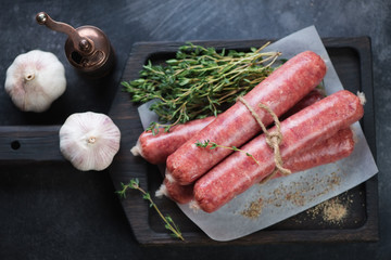 Above view of fresh uncooked marbled beef sausages with fresh thyme and garlic, horizontal shot