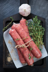 Raw sausages made of marbled beef meat with seasonings, view from above, vertical shot