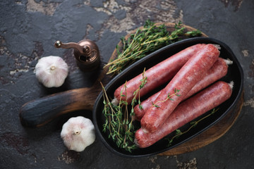 Raw marbled beef sausages with fresh thyme and garlic on a dark brown stone background, horizontal shot, above view
