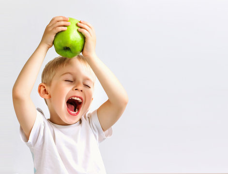 small boy holds a big green apple, healthy food and vitamins, smiling, white background, soft focus
