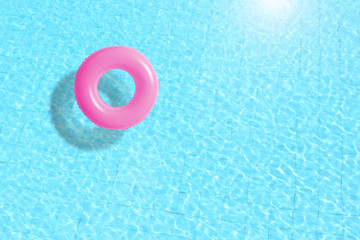 pink swimming pool ring float in blue water. concept color summer.