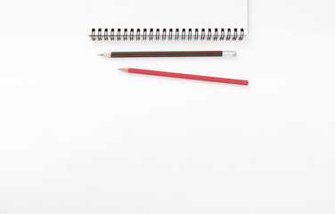 above top view of notebook, pencil on white desk background. blank space for text can used for cover page presentation and web banner.