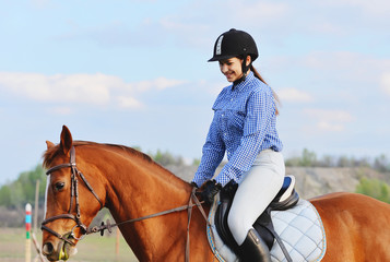 A girl jockey rides a horse