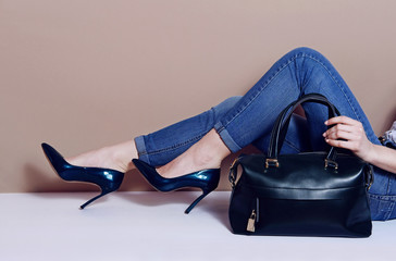female legs lies in jeans blue lacquered heel shoes and big bag