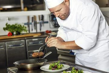 Focused chef prepares steak dish at gourmet restaurant