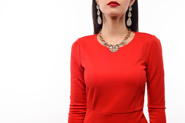 Beautiful woman in red evening dress with necklace and earrings.