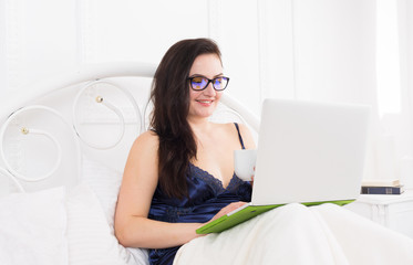 Woman reads from tablet pc in bed, high key