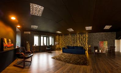 Dark blue sofa, leather armchairs, mirror in stylish loft interior. Photo studio interior