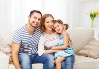 Happy family  laughing and hugging at home on sofa