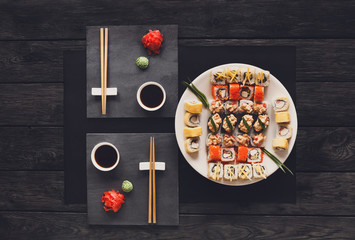 Set of sushi maki and rolls on black rustic wood, top view