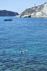 Tremiti Islands. Swimmer in transparent sea water with a boat