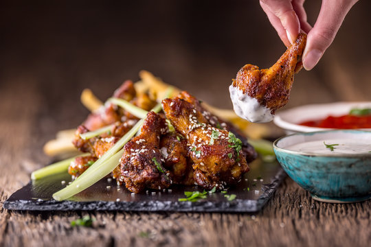 Chicken wings. Fried chicken wings in white bowl garlic dressing ketchup and potato fries.