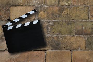 Ciak posizionato sopra a mura composto da vecchi mattoni. Immagine astratta applicabile per industria del cinema, produzione di filmati, inizio attività, startup, nuove sfide e cambiamenti.