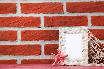 Frame of sea shells with starfish on brick wall background