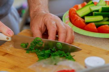 Cut green onion with a kitchen knife on a wooden cutting board. Fresh green onions on a cutting board.