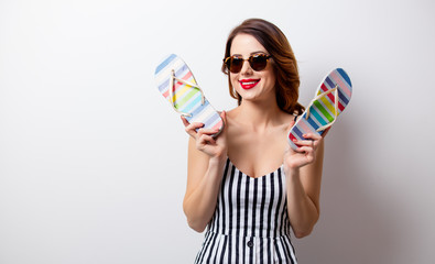portrait of beautiful young woman with sandals on the wonderful white studio background