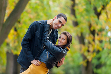 photo of cute couple hugging and smiling on the wonderful autumn park background
