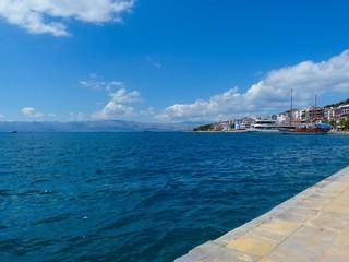 Blauer Himmel mit weißen Wolken über ruhiger See am Yachthafen von Çeşme bei Izmir in der Türkei