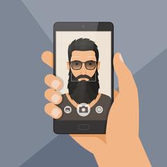 Hipster bearded man lumberjack takes selfie using a smartphone.