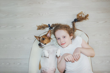 Little girl was embracing a puppy on wood background.