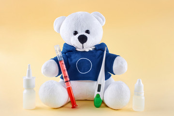 Sick teddy bear with thermometer and bottles of medicinal drugs, on yeallow background.