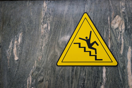 Sign of danger of falling stairs slip warning caution on marble wall