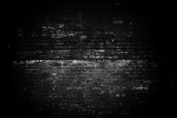 An old gloomy brick wall. Dark lighting, a light spot in the center of the brickwork. Black white empty space. Grunge background