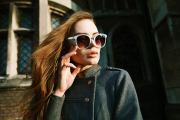 Outdoor close up portrait of young beautiful woman with long hair wearing stylish light blue sunglasses, grey coat posing on street. Model looking aside, touching her face. Female fashion concept