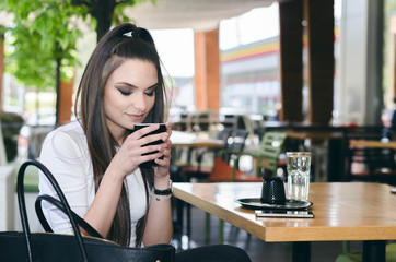young teenager drinking coffee and looking in the cup