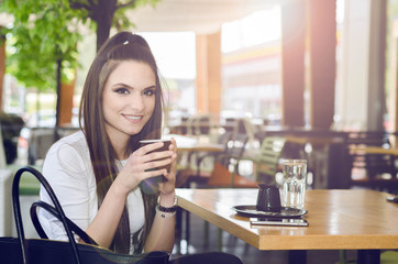 young woman sitting in a cafe, drinking coffee, relax after work and looking at the camera with a smile