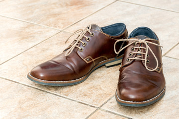 Fashion brown leather men's shoes on a light brown ceramic tiles