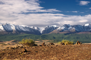 A top high view to highland steppe plateau valley with yellow grass and stones on a background of snow ice mountain ranges and glaciers under white clouds and blue sky Kurai Altai Siberia Russia