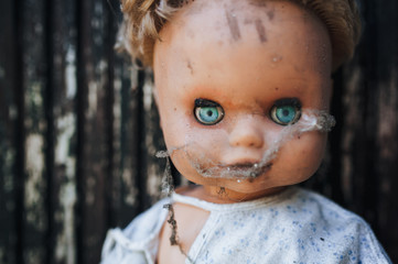 The face of an old doll in a cobweb.