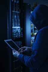 The hacker uses a tablet computer to steal information.